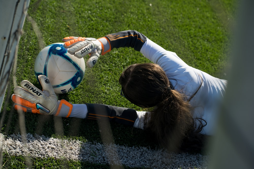 girl in white long sleeve shirt playing soccer on field during daytime