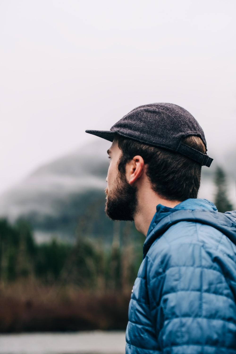 man in blue denim jacket and black cap looking at the mountain during daytime