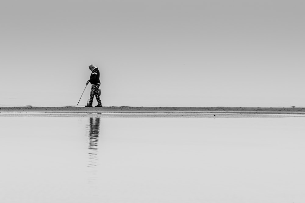 man in black jacket walking on the beach