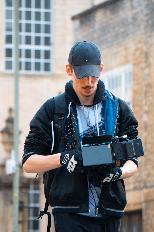 man in black jacket and blue denim jeans holding black dslr camera