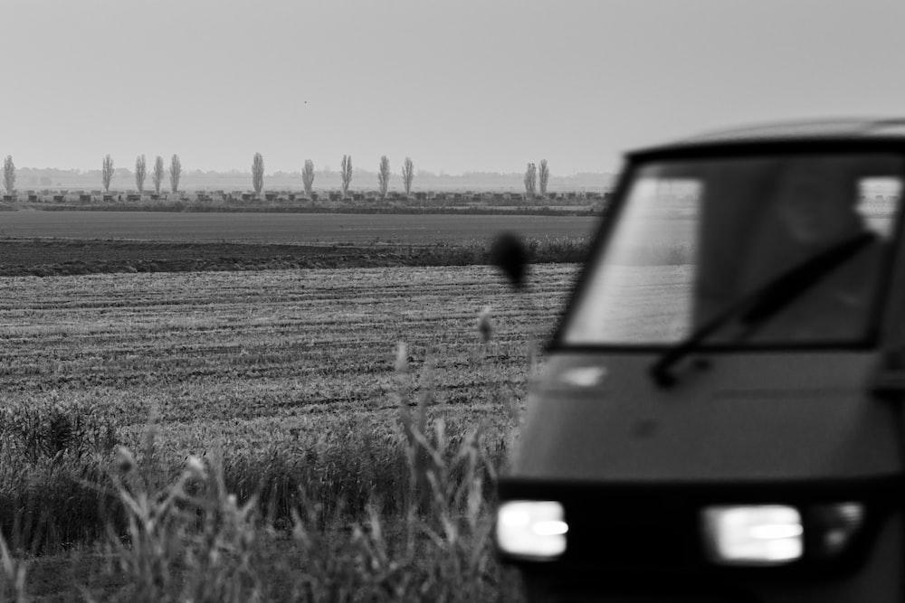 grayscale photo of van on grass field
