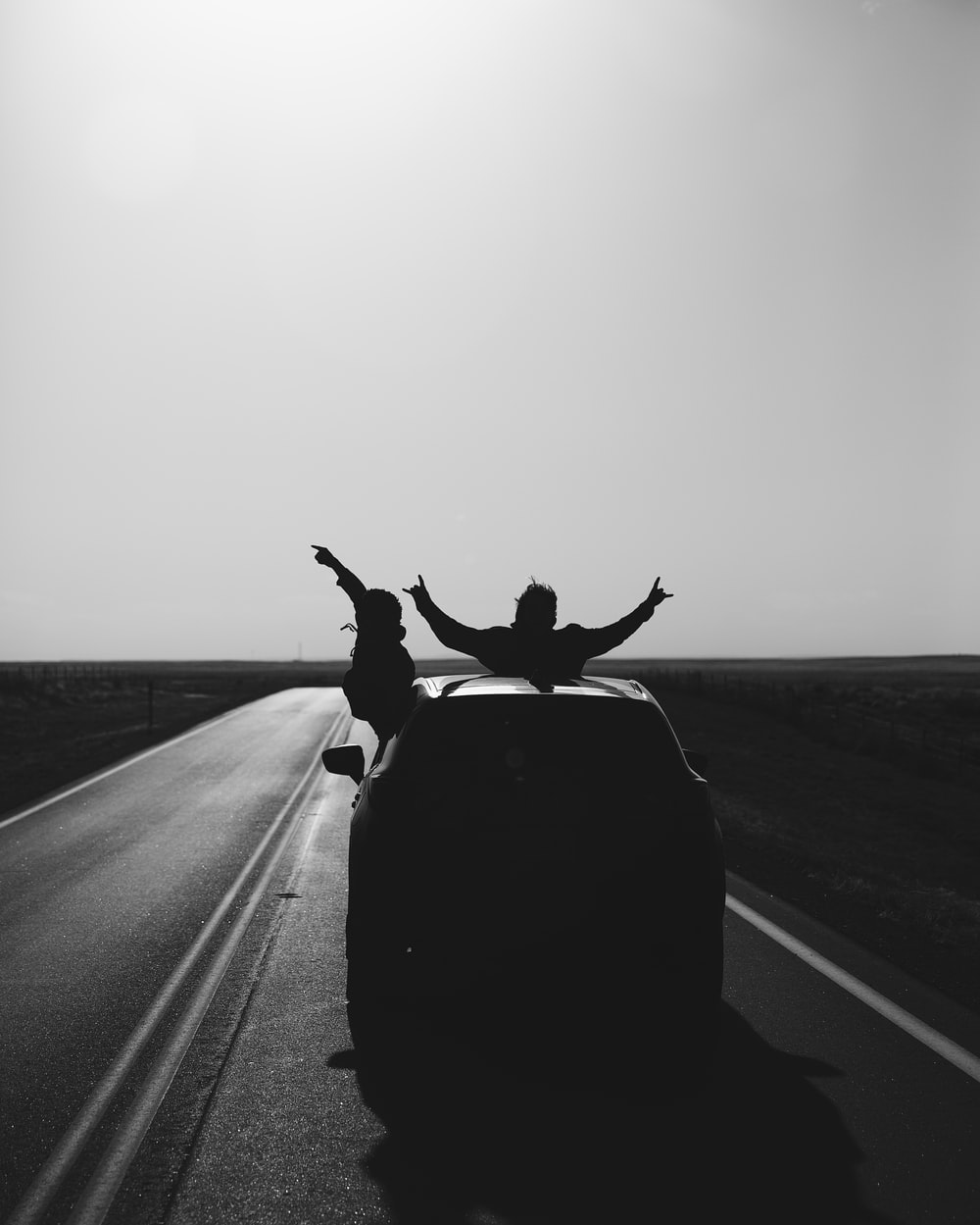 grayscale photo of man riding on motorcycle on road