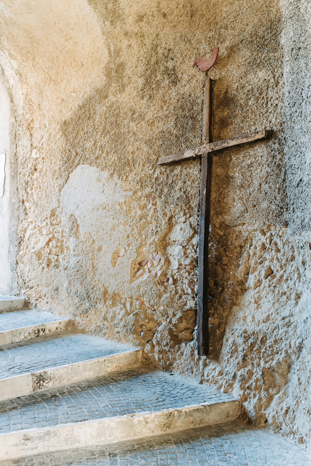brown wooden cross on brown concrete wall