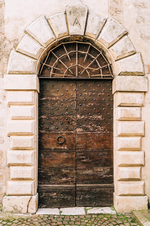 brown wooden door on gray concrete brick wall