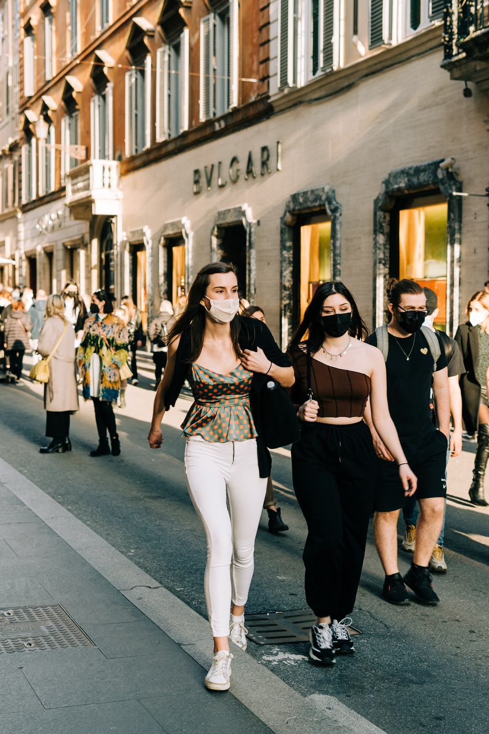 woman in black tank top and white pants standing beside man in black t-shirt