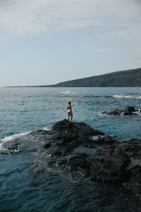 woman in white tank top and black shorts standing on rocky shore during daytime