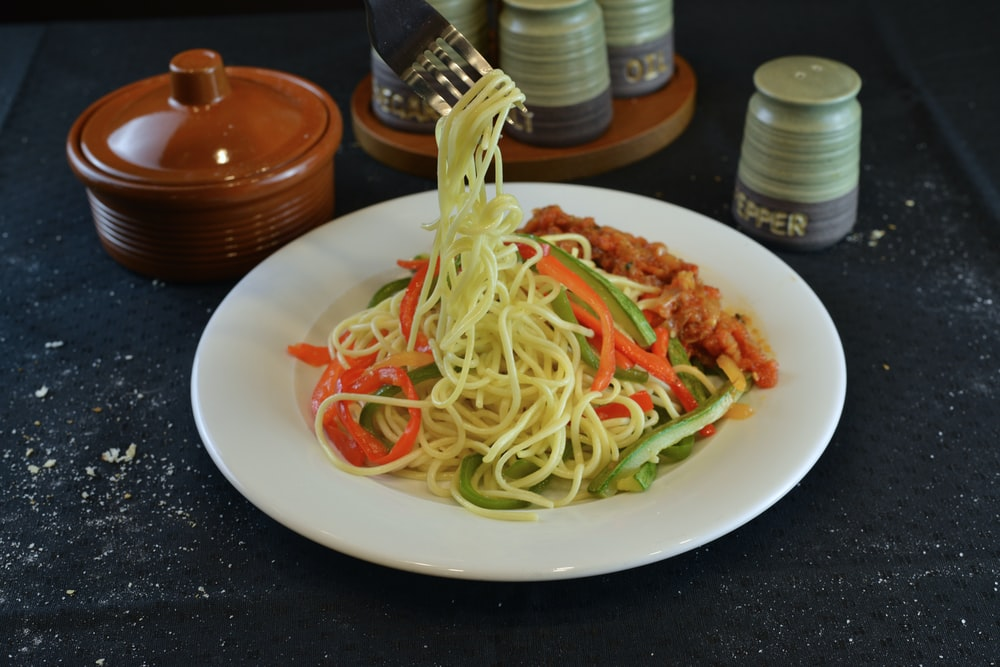 pasta with green leaf vegetable on white ceramic plate
