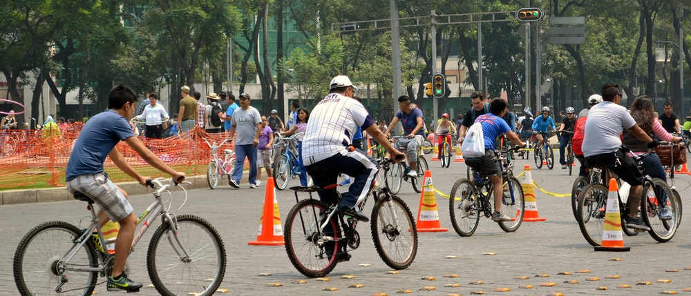 people riding bicycles on road during daytime