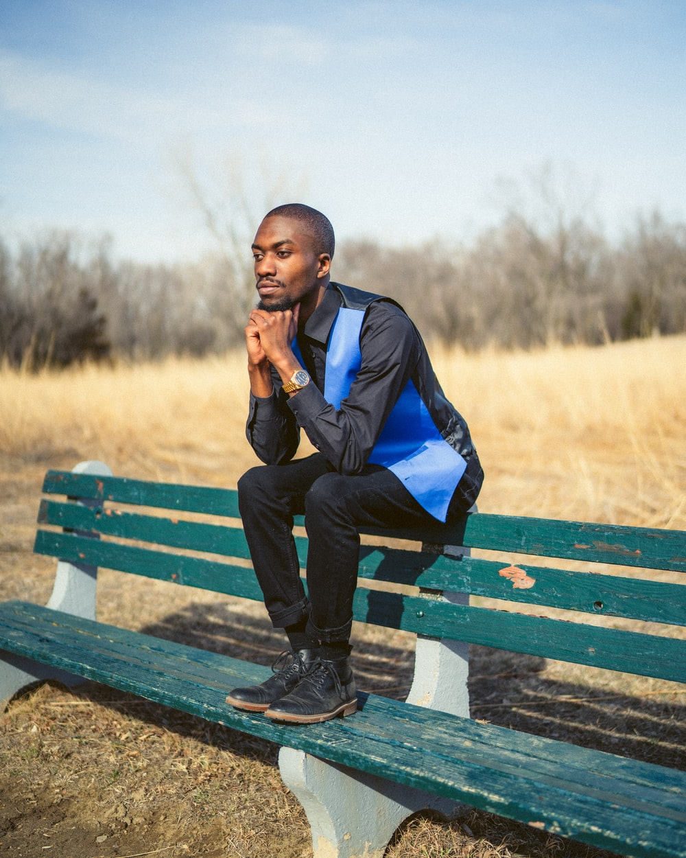man in blue jacket sitting on brown wooden bench during daytime