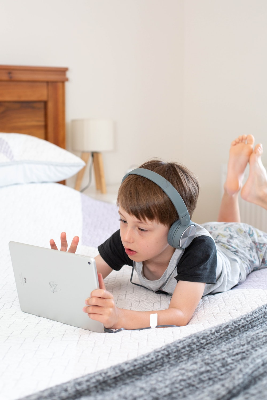 girl in gray t-shirt using white laptop computer