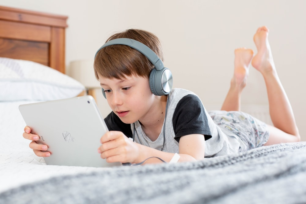 boy in black shirt using white laptop computer