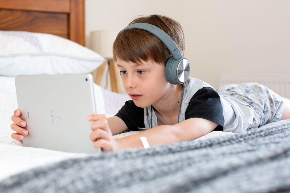 boy in blue shirt wearing headphones lying on bed