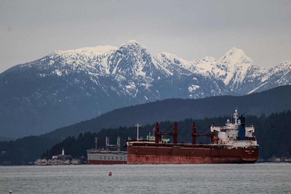 red and white ship on sea near snow covered mountain during daytime