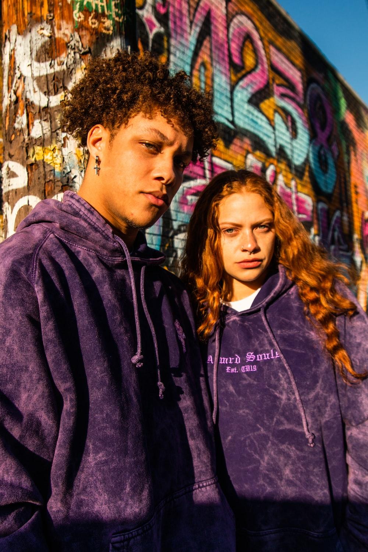 man in purple hoodie standing beside woman in black jacket