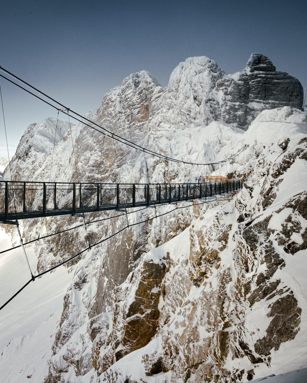 brown wooden bridge over snow covered mountain