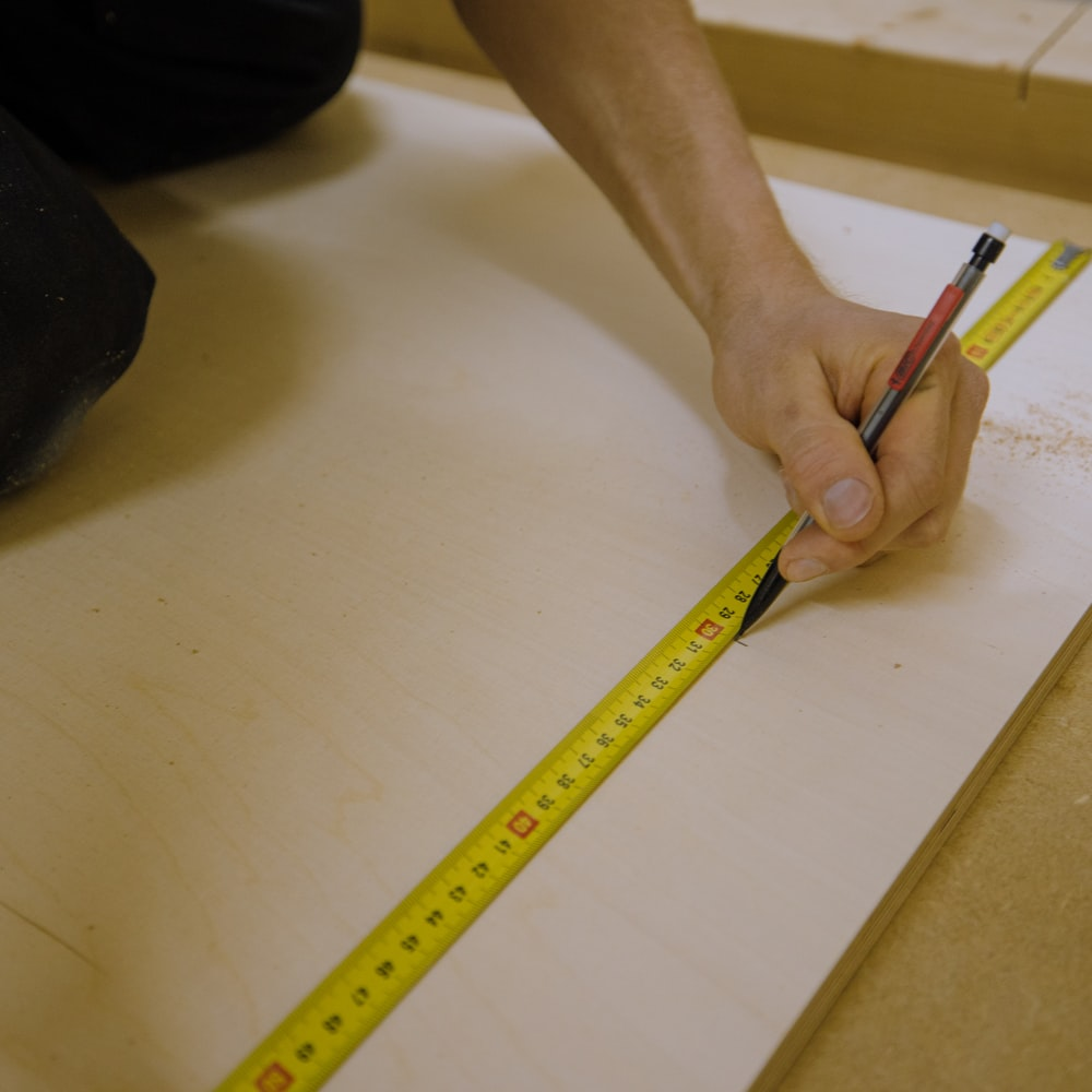person holding yellow pencil on white table