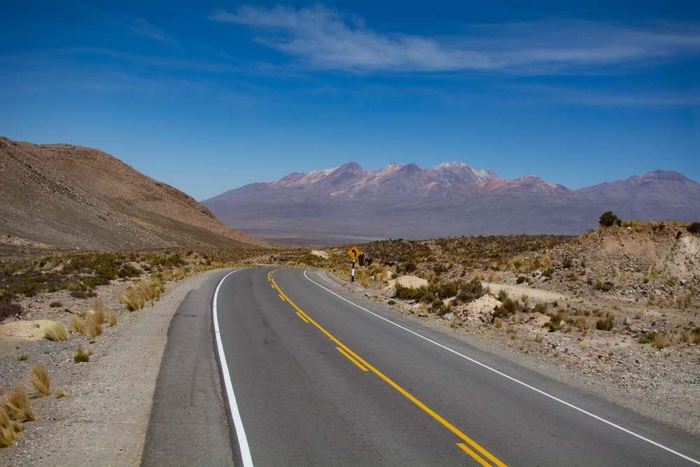 gray concrete road near brown mountains under blue sky during daytime