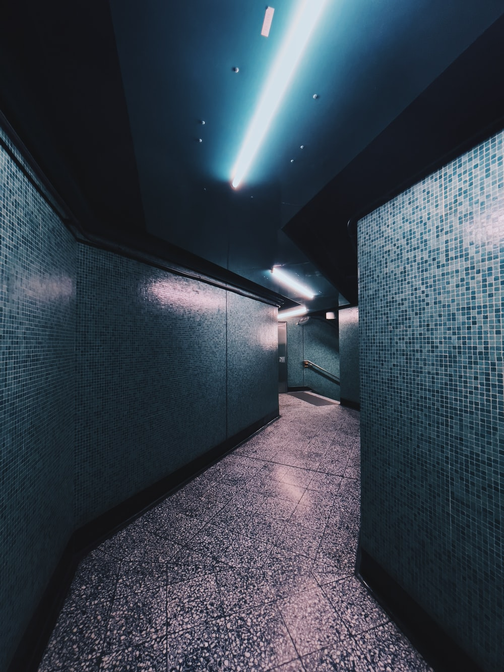 blue and white hallway with lights turned on in room
