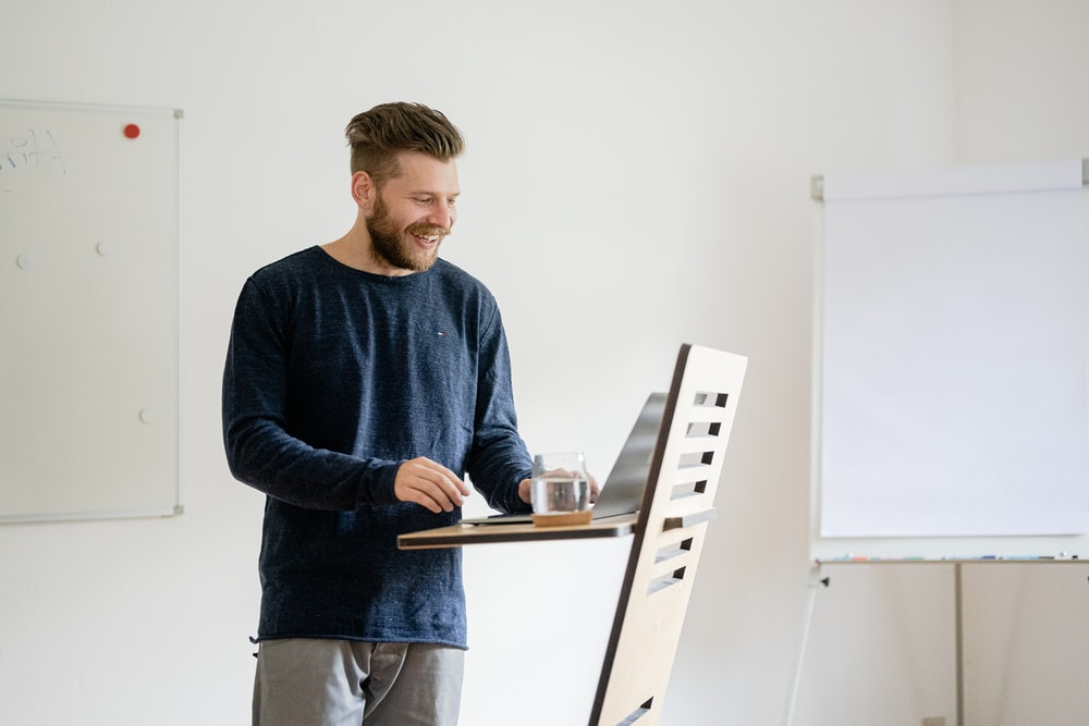 man in blue sweater standing and holding ipad