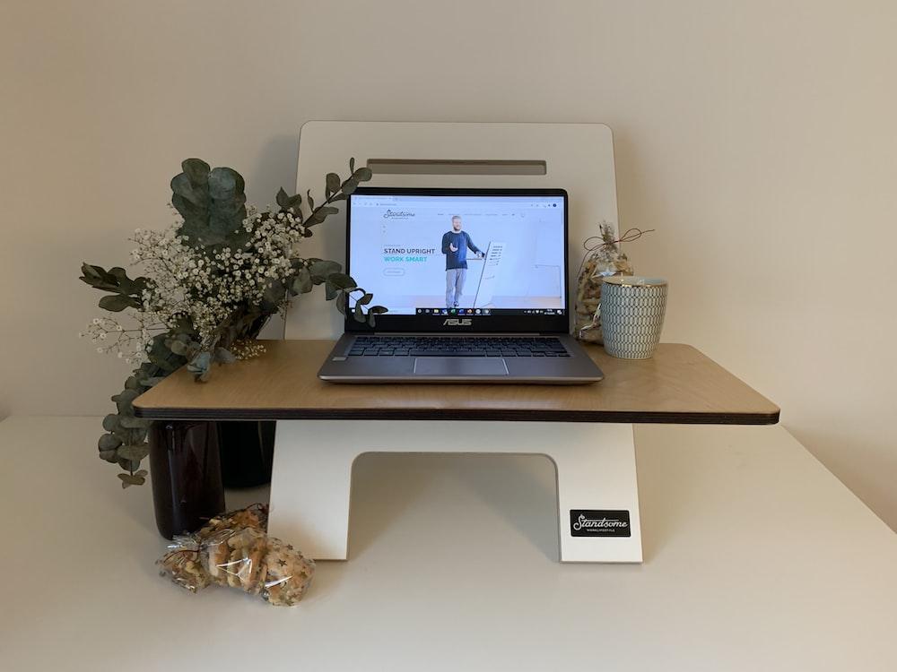 black laptop computer on white wooden desk