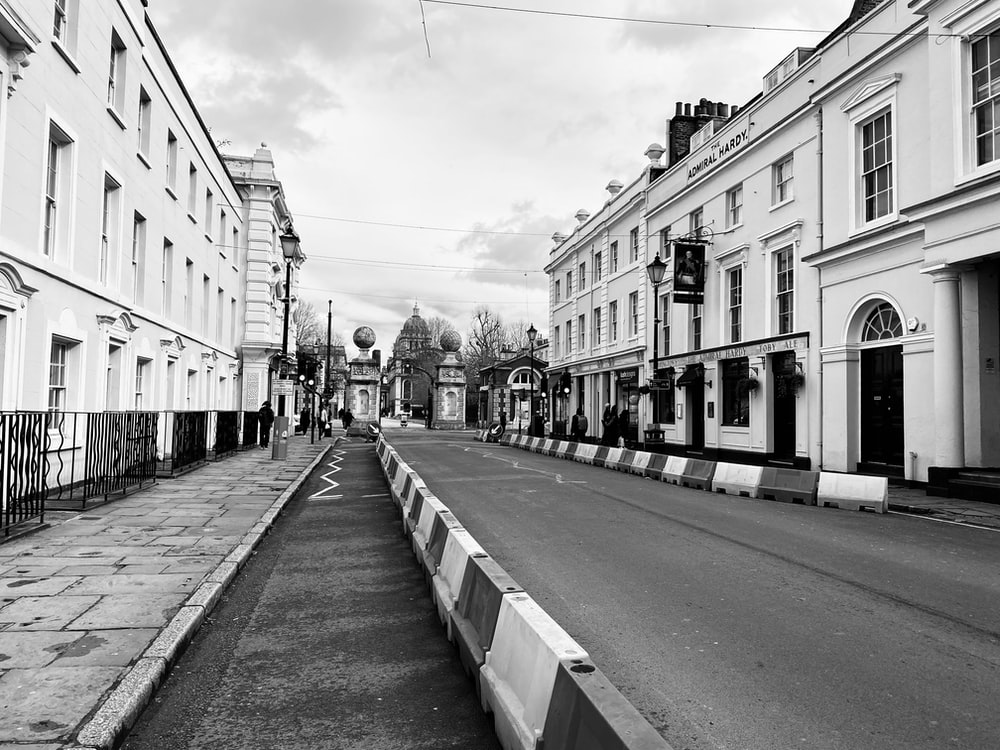 grayscale photo of a street in the middle of a city