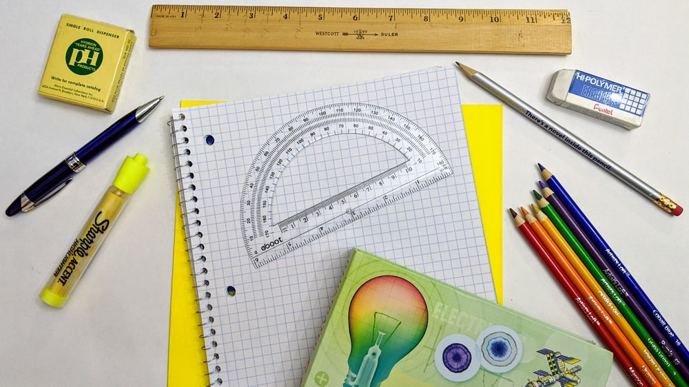green and yellow scissors on white graphing paper