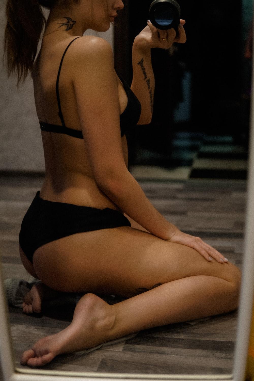 woman in black bikini sitting on floor