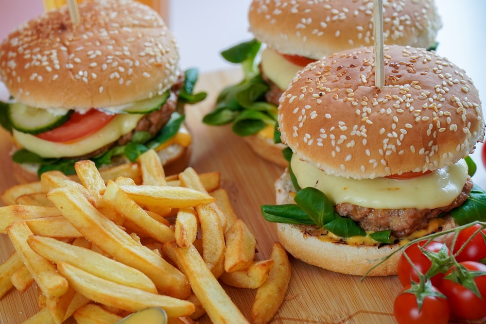 burger with lettuce and fries on brown wooden table