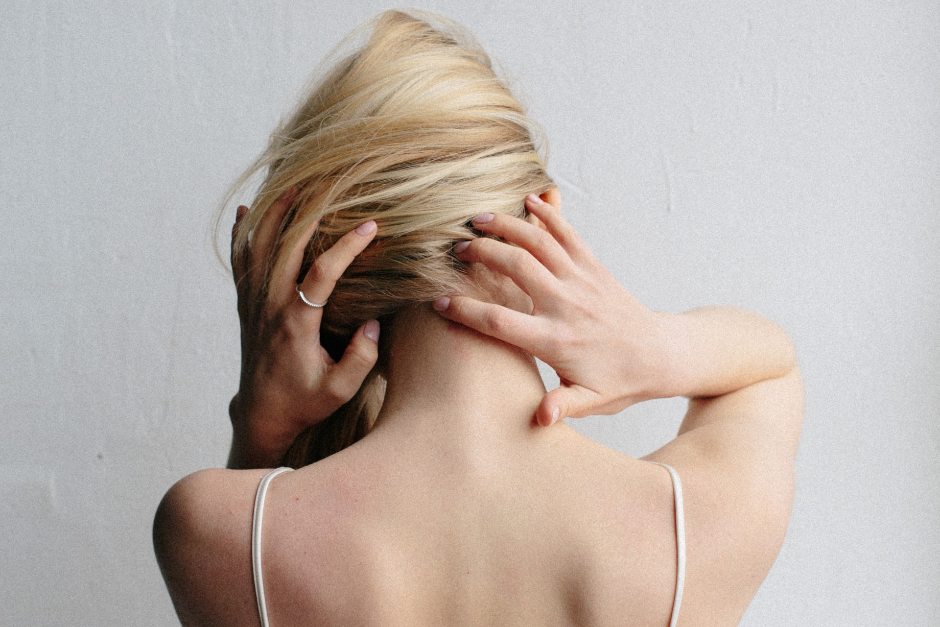 woman in white spaghetti strap top covering her face