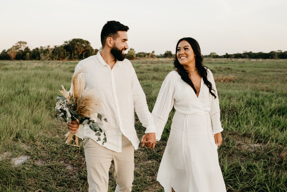 man and woman in white long sleeve shirt walking on green grass field during daytime
