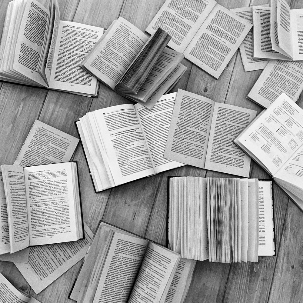 grayscale photo of a book on a wooden table