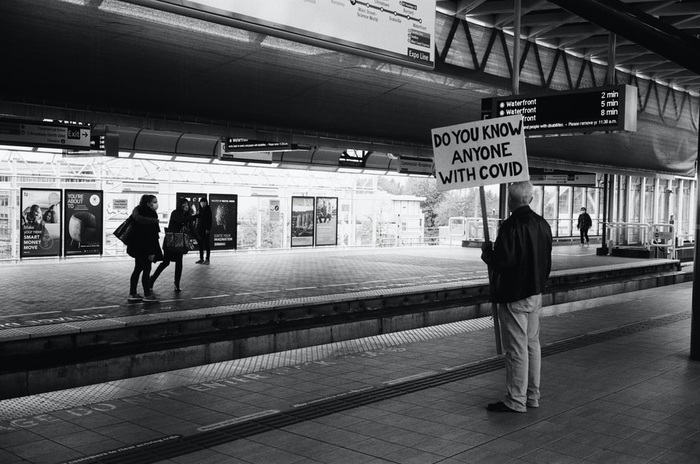 grayscale photo of man in black jacket and white pants standing on train station