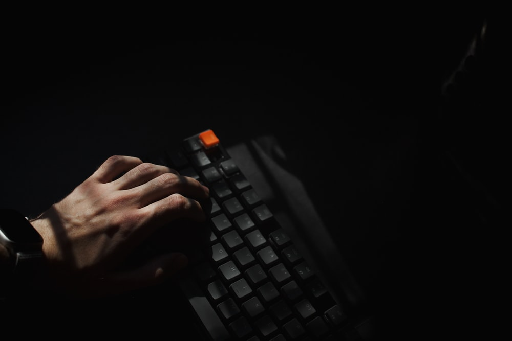 person holding black computer keyboard