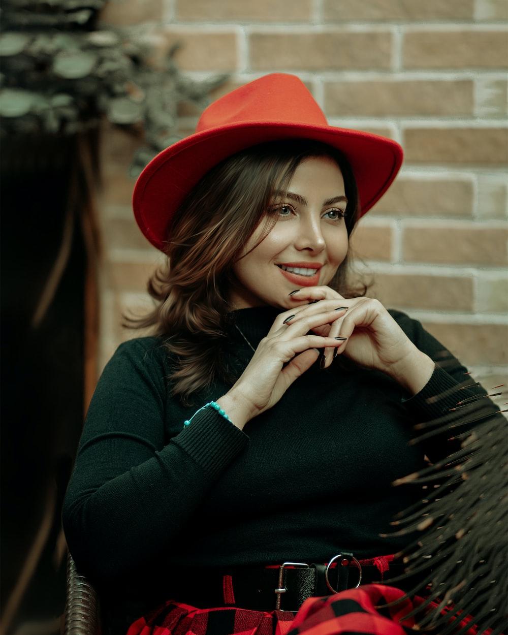 woman in black long sleeve shirt wearing red hat