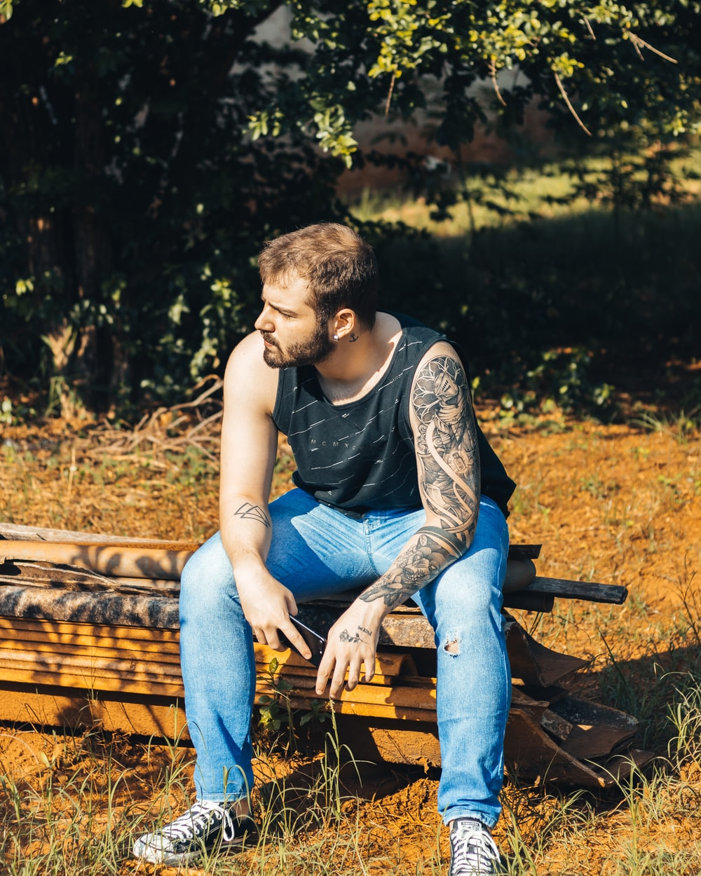woman in black tank top and blue denim jeans sitting on brown wooden bench