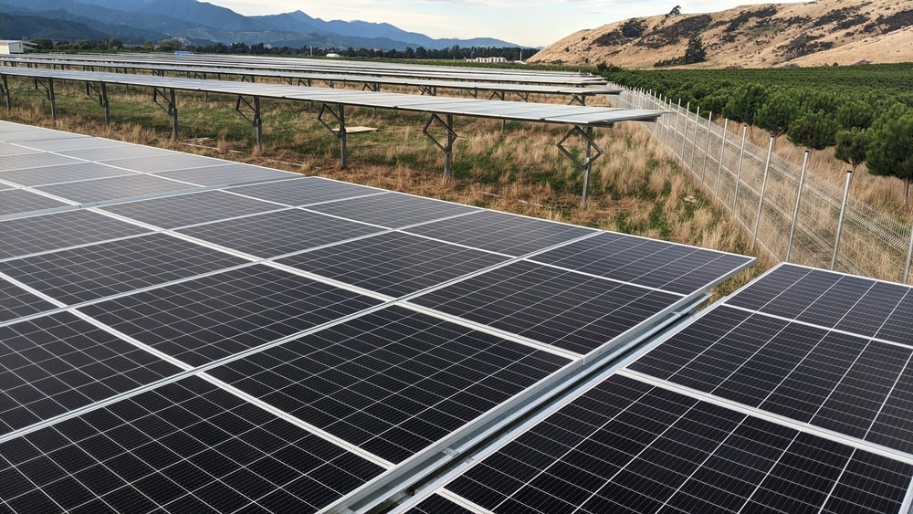 black solar panel on green grass field during daytime