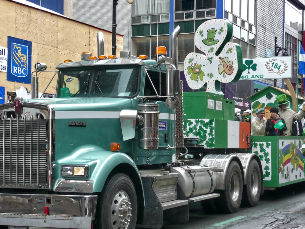 green and white truck on trailer truck