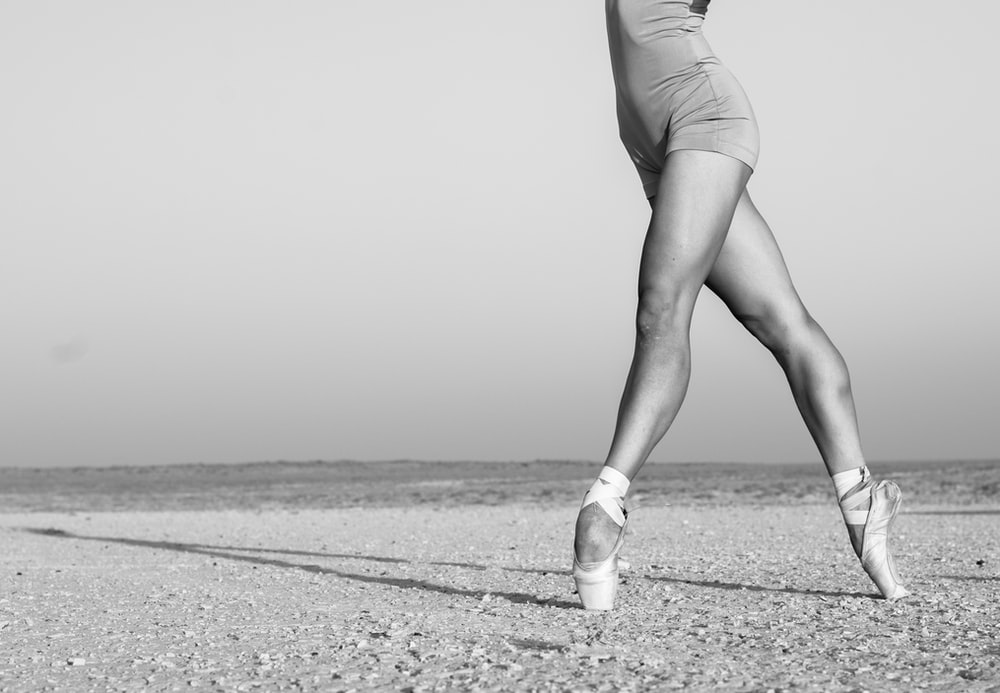 grayscale photo of woman in white tank top and shorts walking on sand