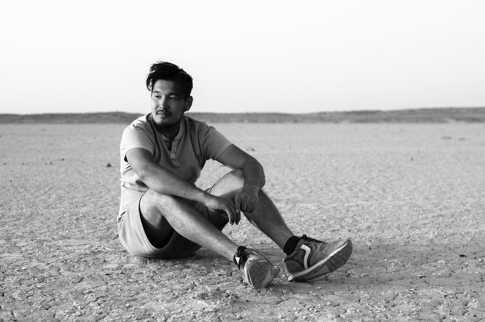 man in crew neck t-shirt and shorts sitting on sand
