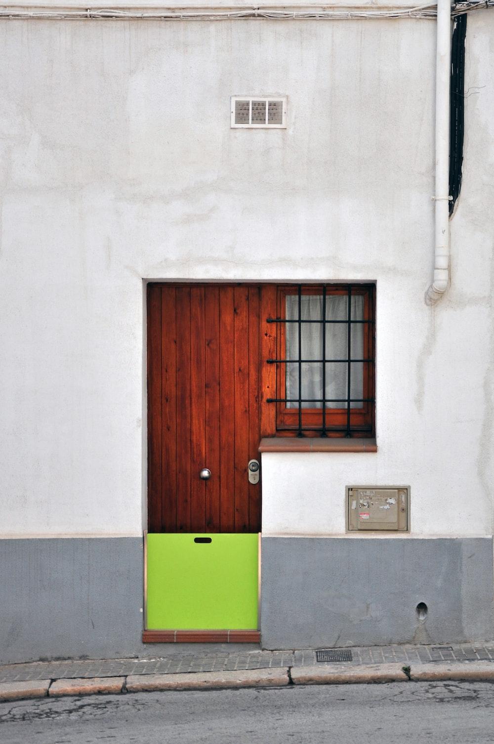 brown wooden door with green and yellow door mat