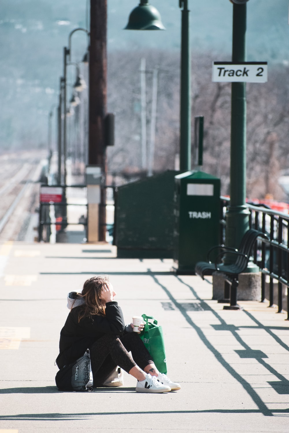 woman in black jacket sitting on bench during daytime