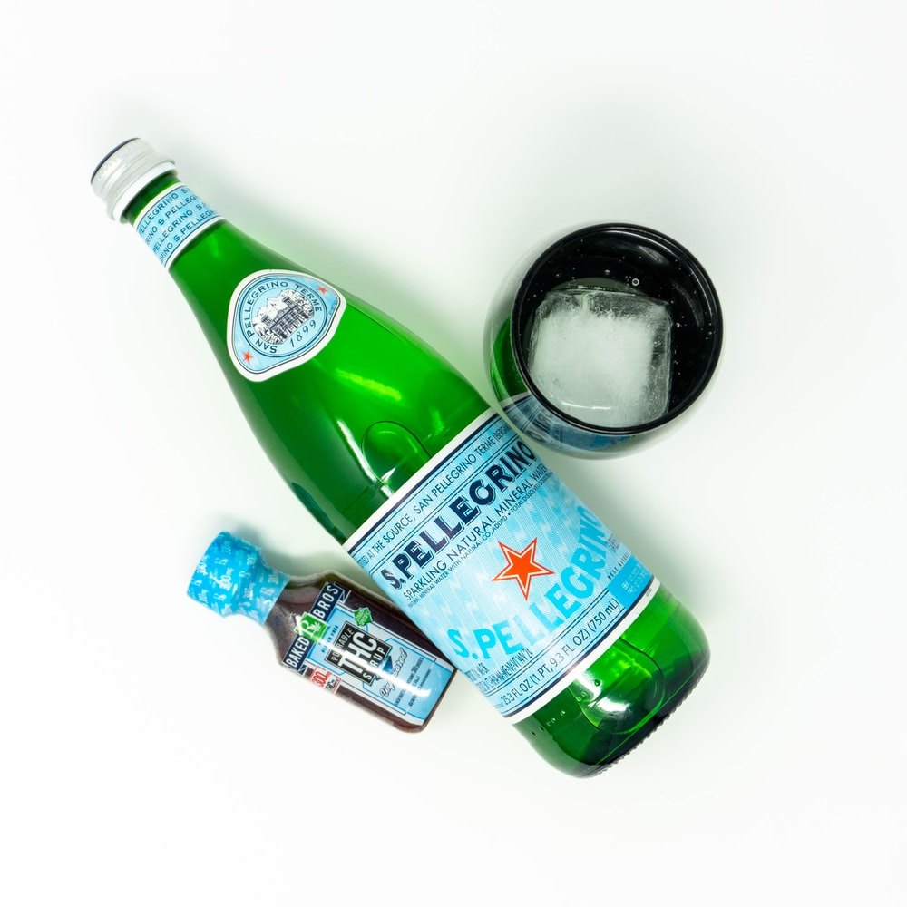 green glass bottle beside green glass bottle