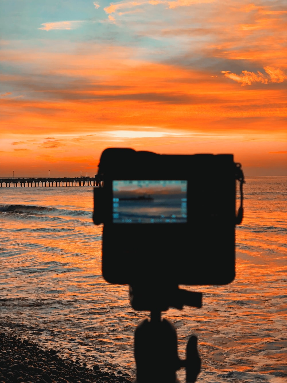 silhouette of camera taking photo of sea during sunset