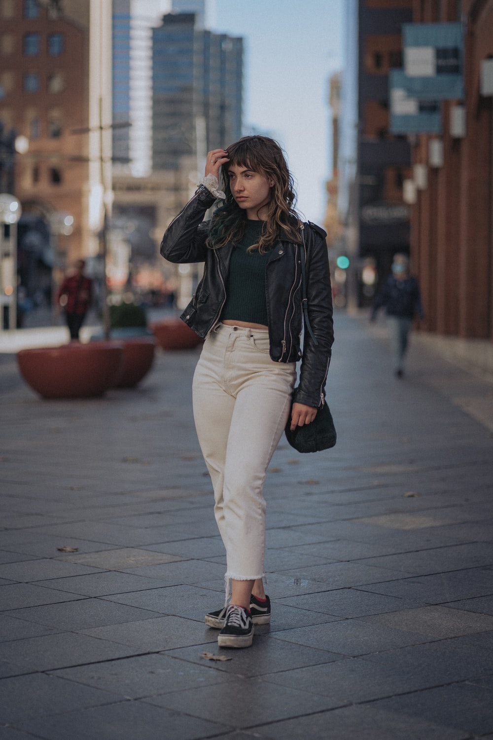 woman in black leather jacket and white pants standing on sidewalk during daytime