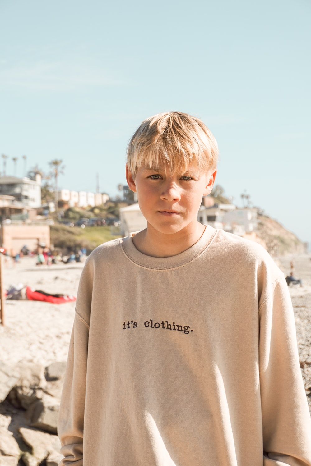 boy in white crew neck shirt standing on brown sand during daytime