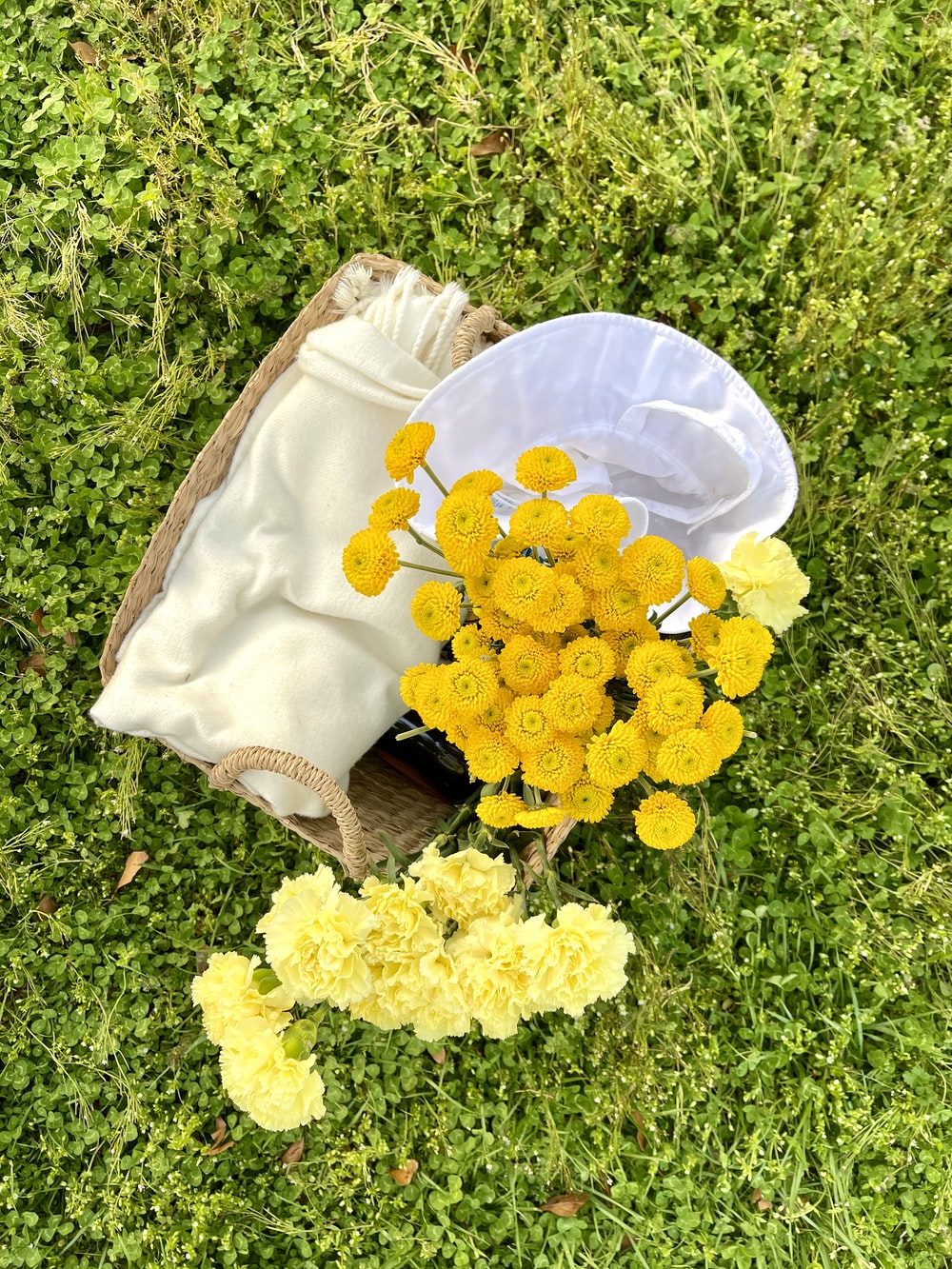 yellow flowers on brown leather bag on green grass field during daytime
