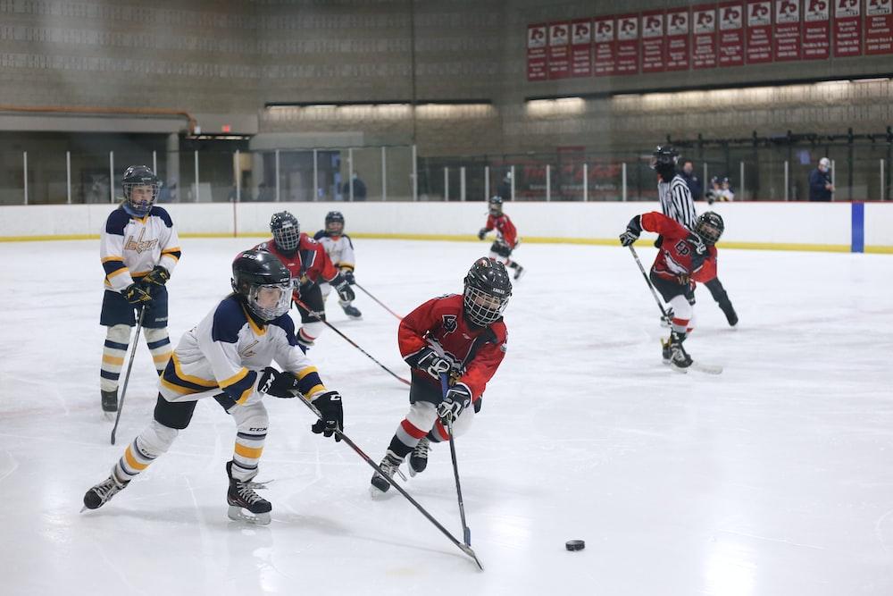 men playing ice hockey on ice stadium
