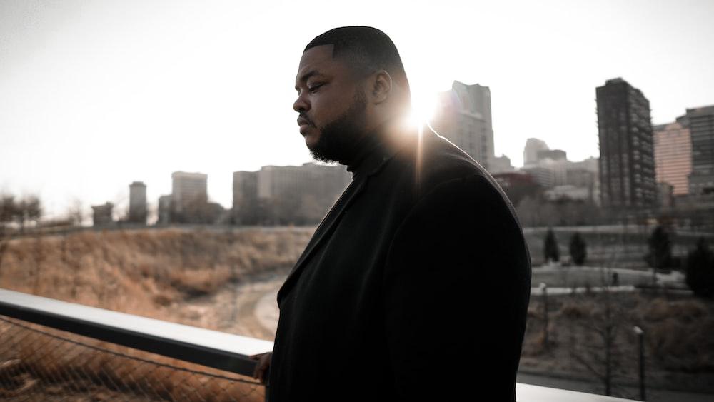 man in black coat standing near window during daytime