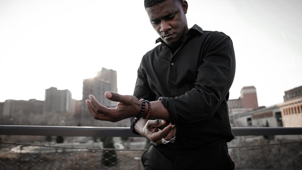 man in black zip up jacket holding smartphone