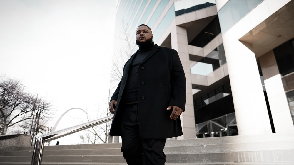 man in black coat standing on gray concrete stairs